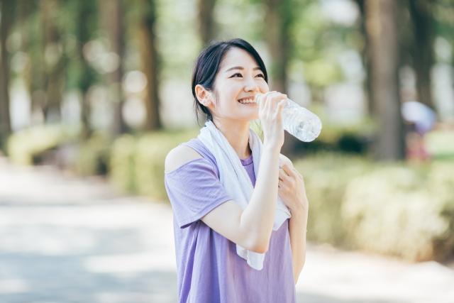 ランニング中に水を飲む女性